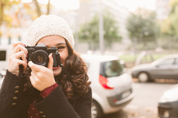 Young beautiful woman with a woolen cap taking pictures with a retro camera in the city in autumn. Focus on camera