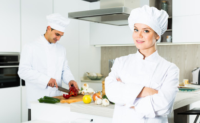 Portrait of woman cook who is standing on her work place in the kitchen