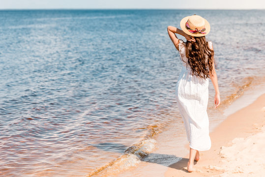 back view of woman in straw hat and white dress walking on beach near sea