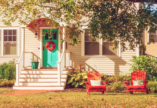 A small cozy wooden traditional American house with wooden chairs by the porch. Autumn sunny day. Vintage style.
