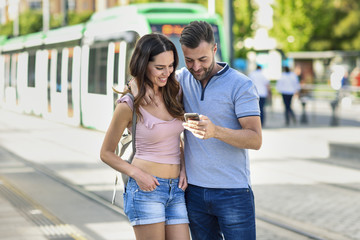 Couple looking at smartphone while waiting for tram at the station