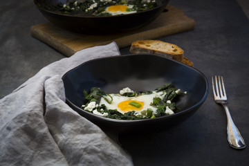 Bowl of green Shakshouka with baby spinat, chard, spring onions and basil