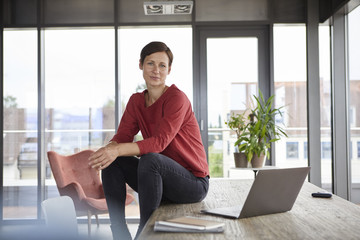 Portrait of woman sitting on table at home with laptop