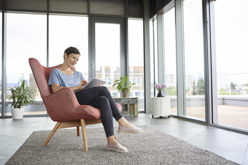 Woman sitting in armchair at home using tablet