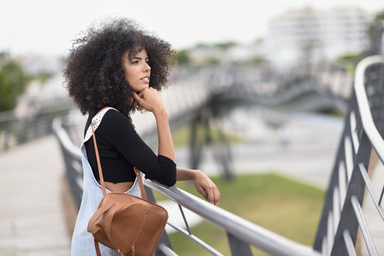 Young woman with brown leather backpack standing on a bridge looking at distance