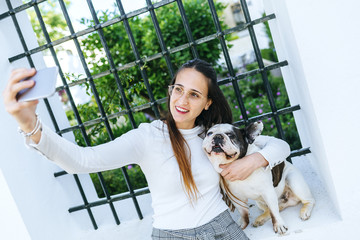 Young woman using smartphone, taking a selfie with her dog