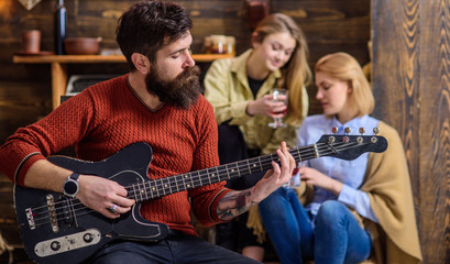 Girls listening to song performed by handsome bearded musician. Guitarist entertaining guests at party. Man with hipster beard playing electrical guitar. Bearded man united with his instrument