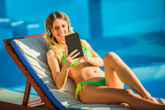 Portrait of young woman in the tropical sun near swimming pool on a deck chair using digital tablet