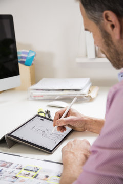 Man working at desk in office drawing female figure on tablet