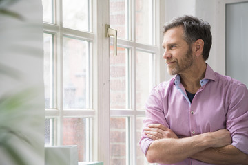 Portrait of a man looking out of window in office