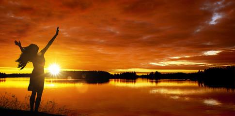 Frau bei Sonnenaufgang am See
