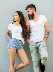 Youth stylish outfit. Feel their style. Couple white shirts cuddle each other. Hipster bearded and stylish girl hang out urban romantic date. Couple friends hang out together grey wall background