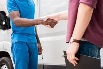 cropped image of multicultural courier and client shaking hands near van