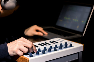 Electronic Dance Music DJ playing song on midi keyboard synthesizer and laptop computer