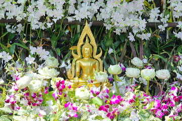 Buddha image on the outdoor cover with   beautiful flowers.