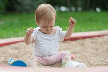 A little girl is sitting in a sandbox on the sand and playing with sand. The kid takes the sand in the palm of her hand and pours it down.