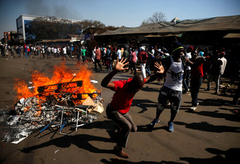 Supporters of the opposition Movement for Democratic Change party (MDC) of Nelson Chamisa react stones as they block a street in Harare