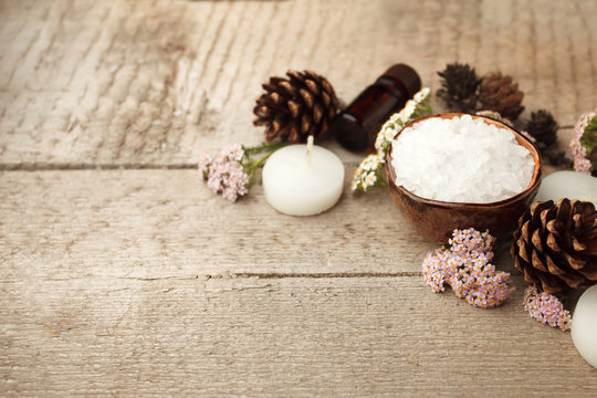 Spa and wellness setting with sea salt, oil essence, cones and candle on wooden background. Fall autumn wellness concept, Relax and treatment therapy. Close up