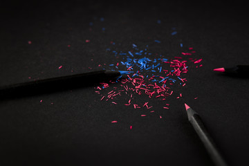 Black, colored pencils, on black background, and shavings from the pencils