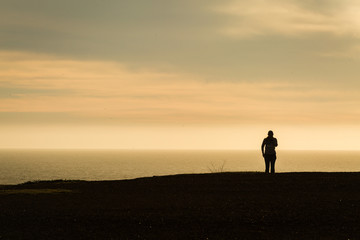 Woman walking along coastal trail taking smartphone photos in silhouette