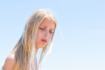 A teenage girl with a frustrated facial expression on a sky background.