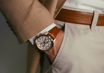 Closeup fashion image of luxury watch on wrist of man.body detail of a business man.Man's hand in brown pants pocket closeup at white background.Man wearing brown jacket and white shirt.Toned.