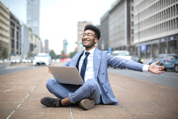 Successful businessman feeling good while working with his laptop in the street