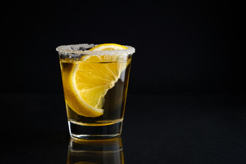 A shot glass of tequila with salt and lime with black isolated background