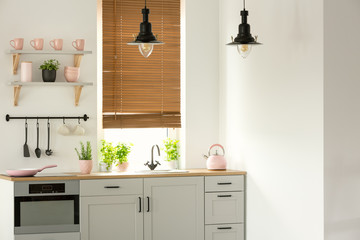 Real photo of a bright kitchen interior with wooden counter, black lamps, white cupboards and pink accents