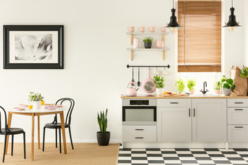Real photo of an open space kitchen and dining room with black and white tiles on the floor, white furniture and pink accessories