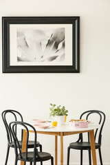 Large, black and white picture of a monstera leaf hanging on a white wall above a round dining table in bright apartment interior. Real photo