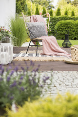 Cozy pillow with pattern and a pink blanket on a garden chair outside on a wooden terrace with rugs and plants