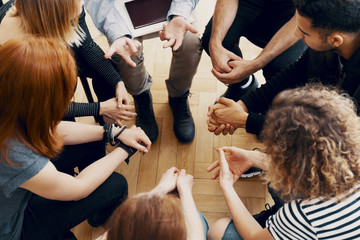 Close-up of hands of teenagers sitting in a circle during a support meeting