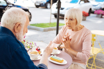 Secret information. Focused senior couple speaking and visiting cafe