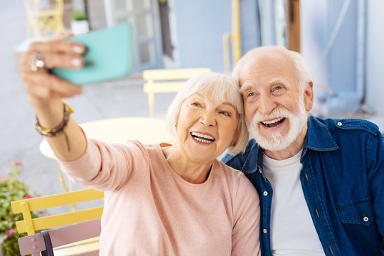 Just smile. Enthusiastic senior couple sitting at cafe and using phone
