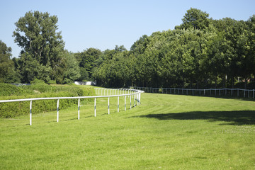 Empty horse racecourse, treated green grass and white rails at the racing track, background landscape with copy space