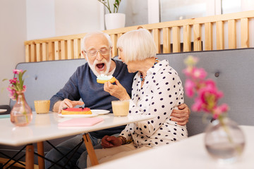 Open mouth. Jovial senior woman holding eclair and senior man biting it