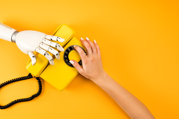 cropped shot of woman and robot reaching for vintage phone on yellow