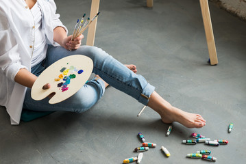 Crop of girl in white shirt and jeans, sitting at work place and creating, drawing picture with oil colorful paints. Pretty woman, female artist holding brush and palette. Concept of art.