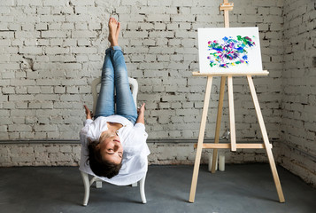 View of seductive and gorgeous young female artist lying on chair near window near picture with oil colorful paints. Beautiful brunette girl in white shirt and jeans with closed eyes, holding legs up.