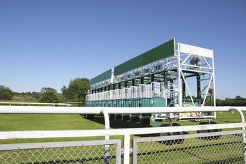 start gate trailer for the horse race on a green grass track at a sunny day against the blue sky, copy space