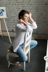 Gorgeous and sensuality young female artist sitting on chair near window and drawing picture with oil colorful paints. Beautiful brunette girl in white shirt and jeans with dirty hands after work.