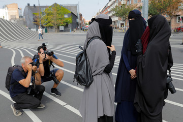 Members of the media photograph women in niqabs before a demonstration against the Danish face veil ban in Copenhagen