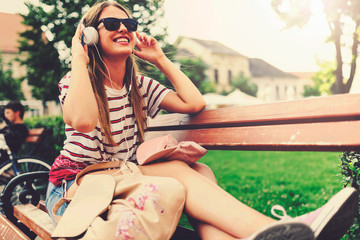 Girl with sunglasses sitting on a bench in the summer listening music over headphones