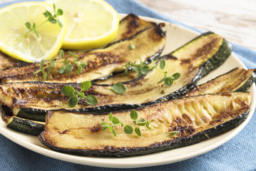 roasted zucchini slices with lemon and herb garnish on a plate, delicious mediterranian vegetables for healthy eating