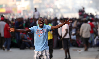 Supporters of the opposition Movement for Democratic Change react as soldiers prepare to disperse crowds outside the party's headquarters in Harare