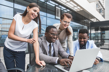 Group of happy diverse male and female business people team in formal gathered around laptop computer in bright office against the background of a glass building