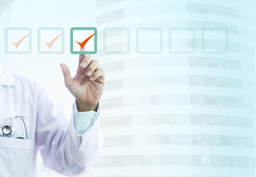 Hand of a male doctor in light-blue shirt and white gown ticks into virtual checklist items indicates that items in the list are correct or have been chosen.