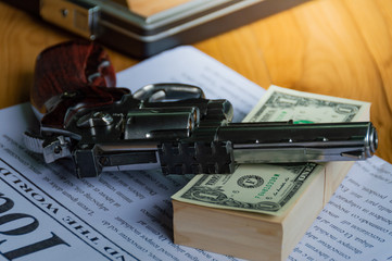 Old guns are placed on bank dollar and newspapers, on wooden table, To dark business concept.