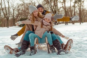 Glückliche Familie fährt auf dem Schlitten